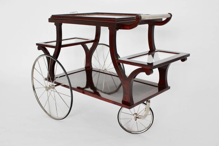 This bar cart was designed and executed, circa 1902 in Vienna. This type of bar cart was used by Adolf Loos for his interiors.  It features three nickel-plated spoke wheels with rubber and nickel-plated fittings. The base is made of solid mahogany,