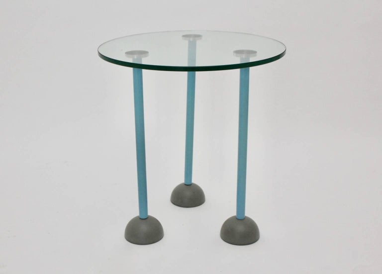 This presented three-legged side table was designed by Ettore Sottsass, 1985.  This side table has three legs in the color turquoise. Each of the feet feature a plastic cup and a wheel. The feet are screwed in metal rosettes so the top is connected