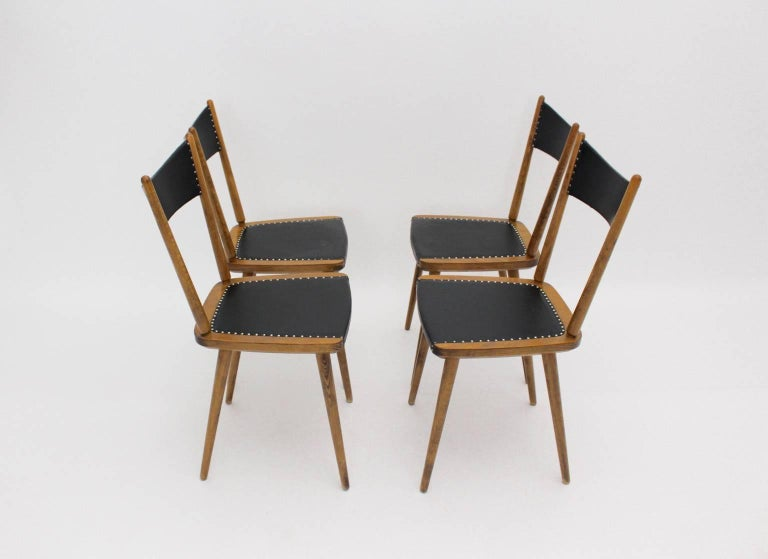 This set of four dining room chairs were made of beechwood. The seat and the back were covered with black faux leather and decorated with decorative nails.  The dining room chairs were designed and executed in Vienna, 1950s. The condition is very