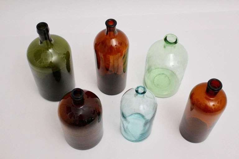 Set of six handblown wine bottles in the color green, brown and colorless with various measures from 2 liters to 5 liters. Diameter from 12.8 cm to 16 cm Height from 29 cm to 38 cm The bottles are carefully cleaned and in best condition.