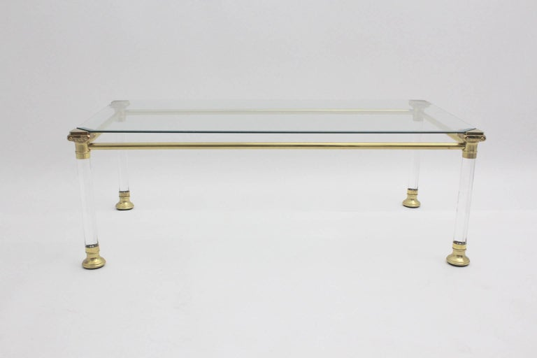 This gorgeous coffee table features four Lucite feet with brass details and a glass top.