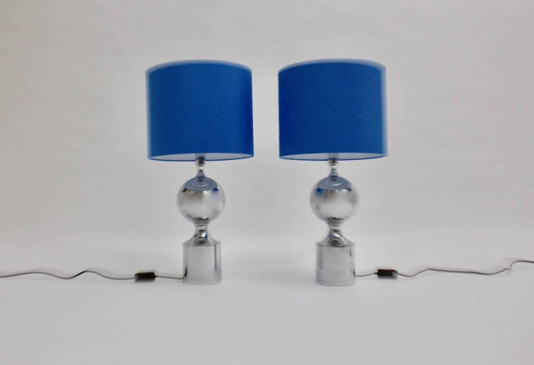 This pair of elegant shiny chromed table lamps were designed in France, 1960s. Both lamps have a renewed lampshade, made of high quality blue silk.  Each lamp has one socket for bulb E 27 and an on/off switch.  The diameter is 35 cm and the