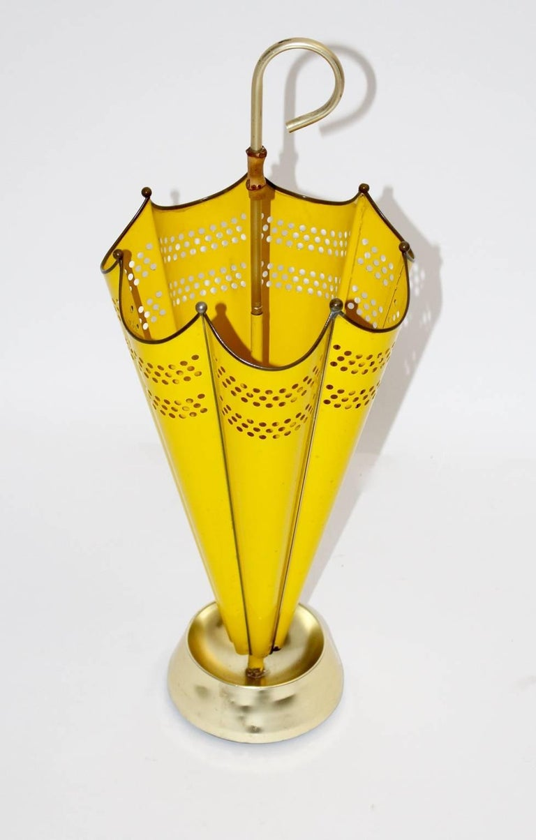 This umbrella stand is shaped like an umbrella. Furthermore it was designed and manufactured during the 1950s, Italy. The umbrella stand was partly made of perforated sheetmetal and lacquered yellow brass. Also it features a cast iron foot covered