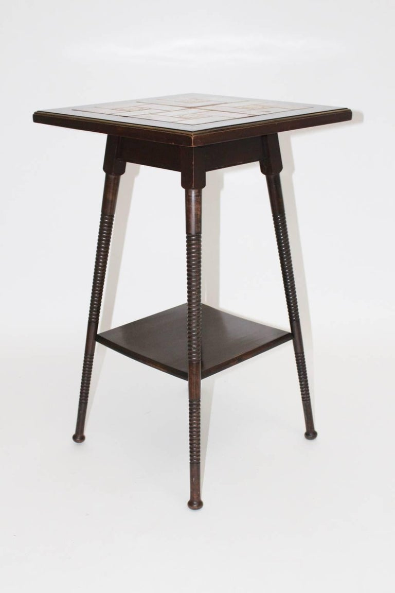 Two-tiered side table, beechwood brown stained with turned legs. The top shows the original green and redbrown ceramic tiles and a brass edge. This kind of side table was used by Adolf Loos for his apartment.  Literature: Adolf Loos; Burkhard