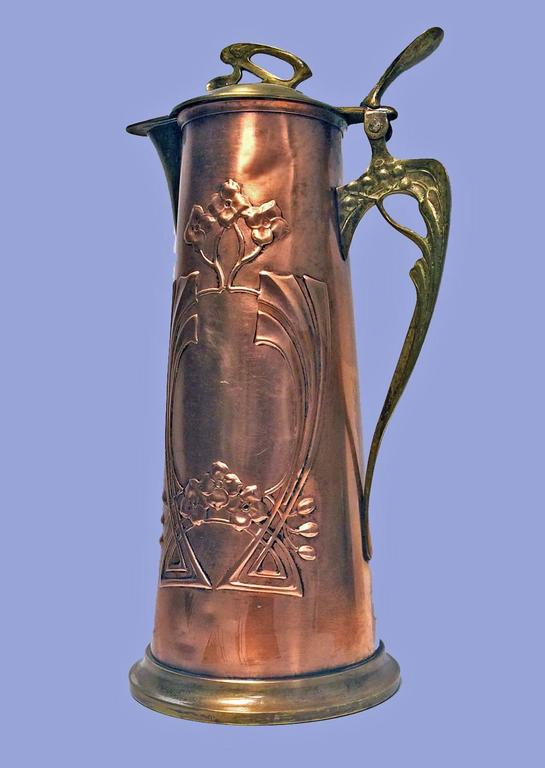 Arts & Crafts copper and brass pitcher jug, probably, Germany, circa 1900. The slightly tapered jug decorated with motifs in celtic manner and stylized handle and thumb piece, plain moulded base, hinged dome shaped cover, stylised thumbpiece.