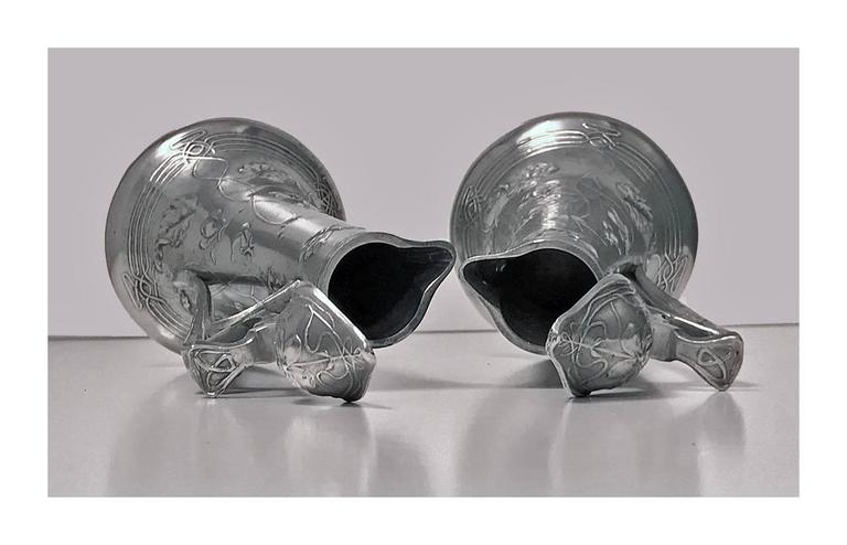 Pair of Art Nouveau Pewter liquor jugs, Germany, circa 1900. The tapered jugs on flared bases with trailing ivy leaf pattern decoration. The dome hinged covers and thumb piece conforming in design, stylized whiplash handle. Measures: Height 6.75