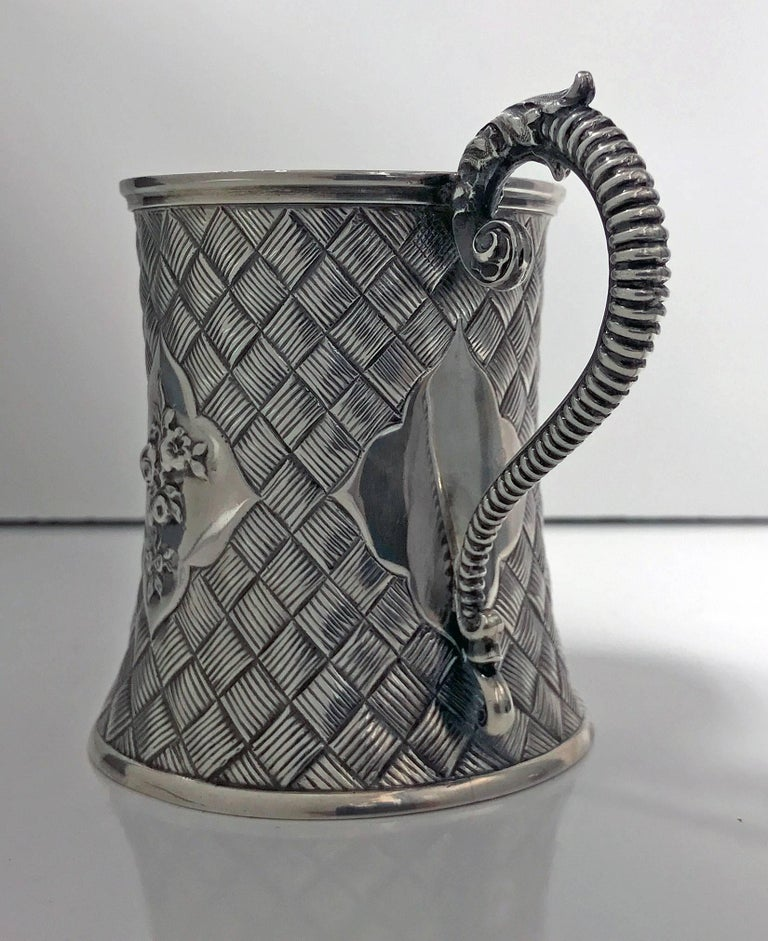 Antique Victorian silver mug, London 1863 by Robert Harper. The mug with tapering cylindrical body embossed and chased with weave design latticework around, centring four cartouche shaped panels, the centre panel engraved with initials and engraved