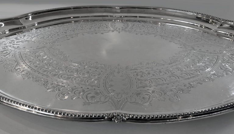 Antique Victorian silver plate two handled tray, Walker and Hall, circa 1890. The large oval tray on four turned supports, raised outer bead rim and open lobate handles. The centre plain with a surrounds of engraved foliate decoration. Stamped with