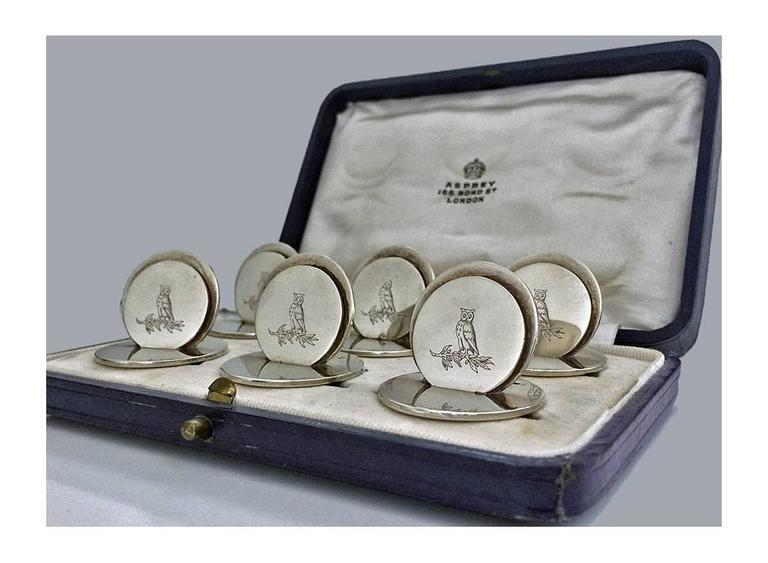 Set of 6 Silver Place Card Holders, London 1931, Asprey & Co. Original fitted box. Each of circular disc like form, engraved with the crest of an owl. All fully hallmarked and stamped Asprey London. Measures: 1.25 x 1.0 inches. Total Item Weight: