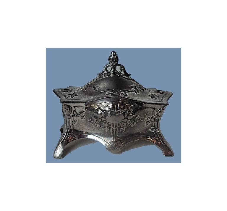 Art Nouveau Silver plate Jewellery Box, Germany C.1900 by WMF. The casket box on four turned supports, the undulating body with floral foliate decoration, the hinged cover similarly decorated with stylised bud finial., original lining. WMF Marks
