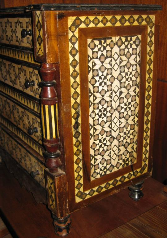 Petite size antique chest handmade of African pine with fruit wood inlay in an intricate design accentuated with black painted wood. Featuring much detail including triple feet, turned front columns and a carved bottom apron, this handsome piece is