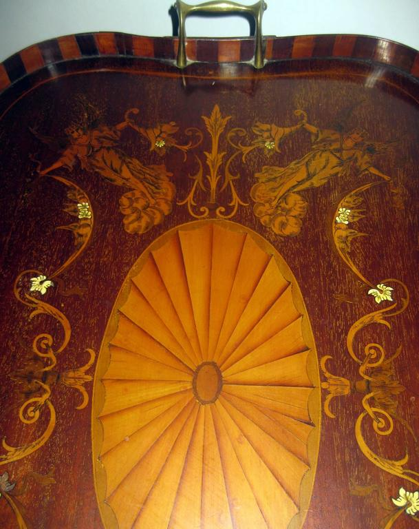 English mahogany tray with fanciful inlay and unusual curved wood gallery. Featuring four angels bearing cornucopias with scroll work around a centre medallion and graceful brass handles, this fabulous one of a kind piece would make a lovely tray
