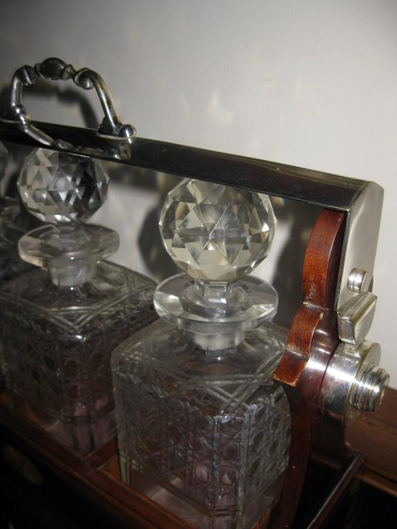 English mahogany three decanter Tantalus featuring silver handle and locking mechanism top. The original cut-glass decanters with stoppers are in a fitted case with cross band inlay on panels with corner and centre shell medallions. Exquisite