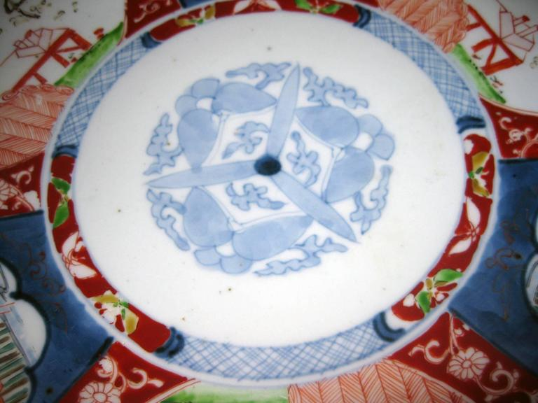 Petite Imari charger featuring a center medallion with butterflies. The edges are painted with intricate geometric, floral and bird motifs in lovely pale colors. Designs painted on back of charger as well.