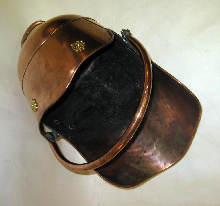 Scottish Helmet shaped coal scuttle/ hod with nice form, shape and size. Adjustable handle riveted to back with applied brass ornamentation at top.  Measures: 16 inches tall when handle is up-14 inches when down. See other measurements below.