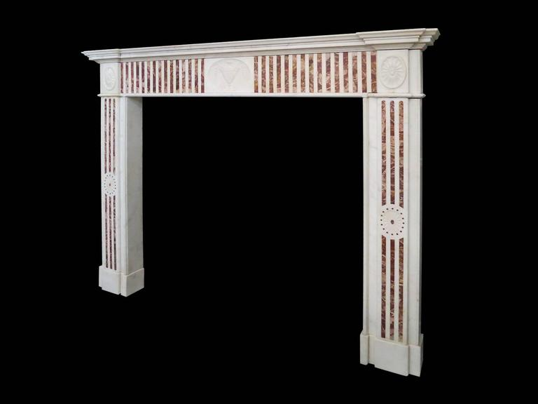 An Irish, George III period surround in Statuary white and Sicilian Jasper Marbles.  The pilaster fluted jambs with Jasper inlay and carved elliptical rosettes. The centre tablet of carved classical urn flanked either side by conforming Jasper