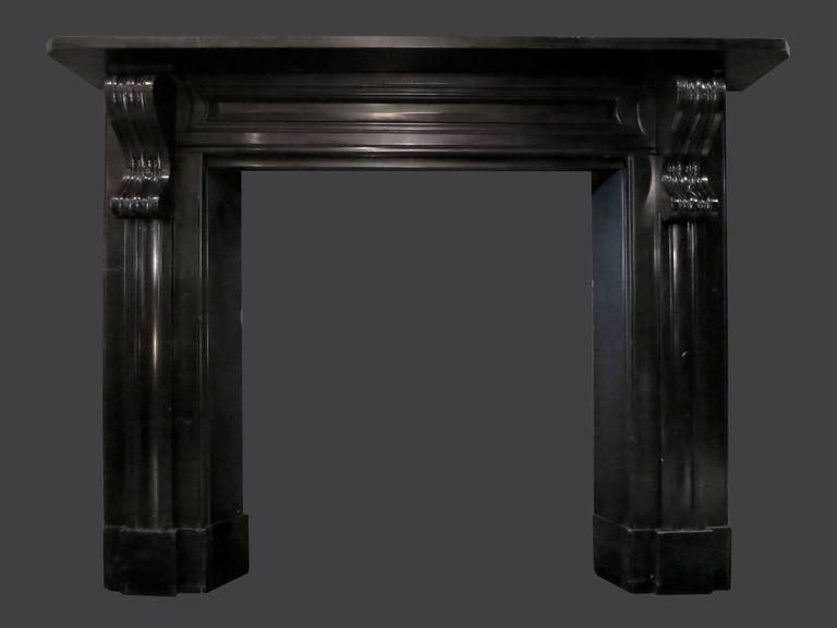 A large sophisticated mantel in black Kilkenny marble. From Rathvilly, County Carlow. The jambs with moulded panels and large deeply carved Irish Corbels, supported on separate foot blocks. The inverted inner slips being deeper than the outside