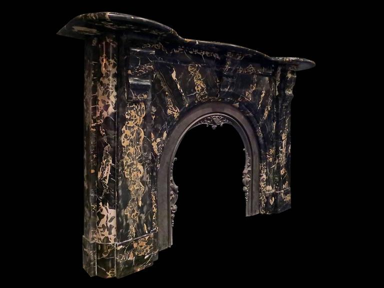 A large and substantial arched Irish fireplace in rare, superior quality and highly variegated Italian portoro marble. The simple panelled Jambs with cushion moulded sides and carved brackets supporting a very large serpentine mantel. The arch with