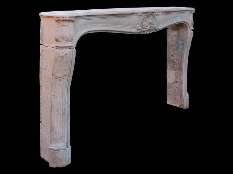 A large and well proportioned surround, carved in French limestone. The cantered and panelled jambs supporting a wide panelled prize with carved shell cartouche to centre, with conforming scrolled and panelled end blocks. All beneath a large