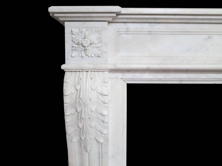 A 19th century Louis XVI style fireplace in Italian Carrara marble. The frieze with carved oval patarae to centre with fielded panels on either side. The end blocks again of carved patarae atop acanthus leaf carving on console shaped jambs. Having