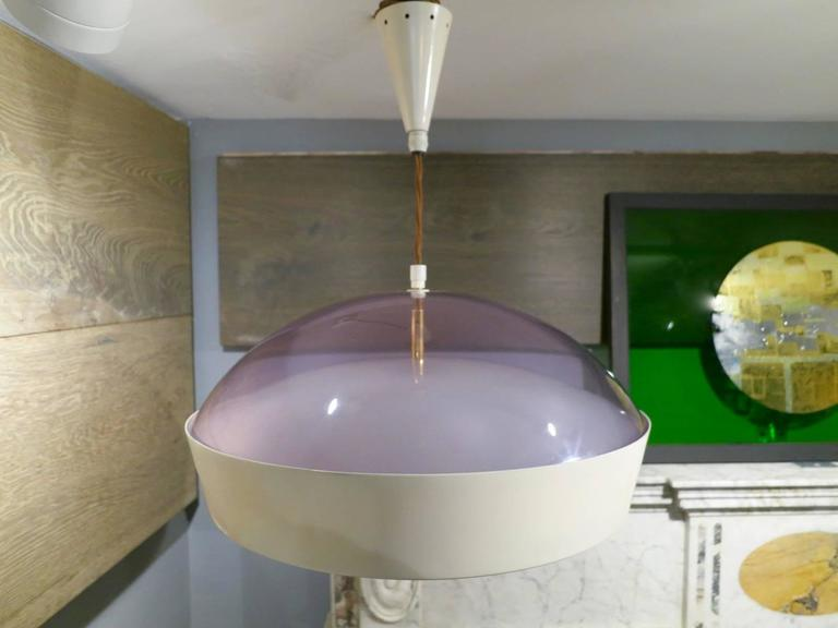 A circular domed topped pendant in white lacquered metal with frosted glass shade beneath and purpled domed top above. Having six light fittings and brass accents. The silk cord allowing a much longer drop if required. A well designed and quality