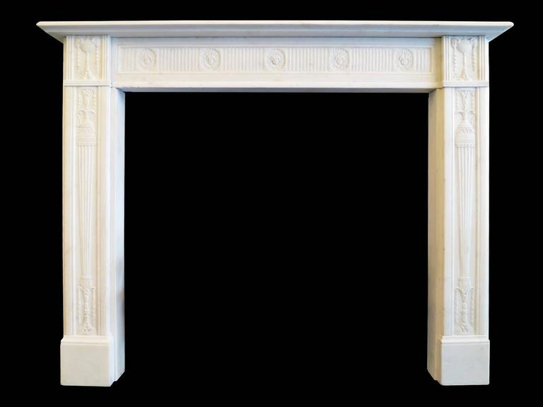 A very fine and well proportioned mantel in Statuary white marble. The jambs having carved tapering pedestals, bell drops and drapery. The corner blocks of classical ram's head urns again with descending bell drops, flanking a running carved bow