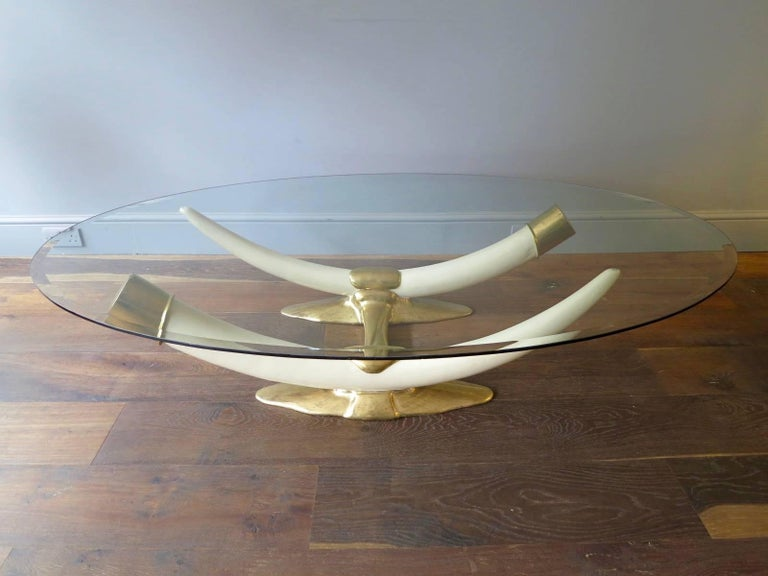 A rare and signed coffee table by Duval-Brasseur, with gilt bronze base, resin faux tusks and oval shaped glass top.