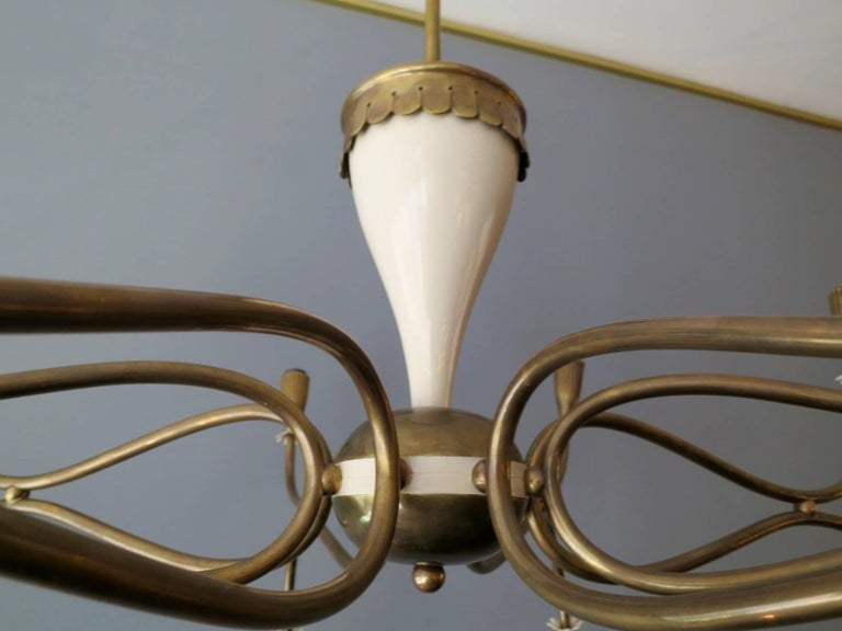 A large sixteen arm chandelier in brass with cream lacquered accents. The reeded bulb holders capped with cream petal shaped decoration, facing both up and down. The centre in brass and cream lacquered body. A very good quality piece in superb