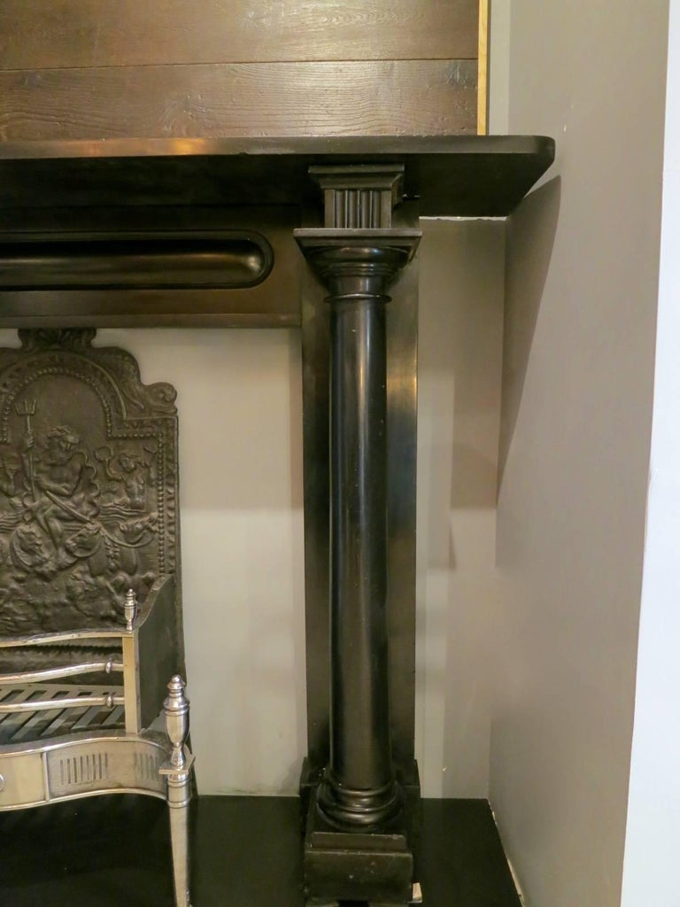 A substantial and superior quality chimney piece in black Irish Kilkenny marble, early 19th century Regency period fireplace, with fully detached columns supported on square footblocks, surmounted by square fluted cornerbacks. The frieze with a