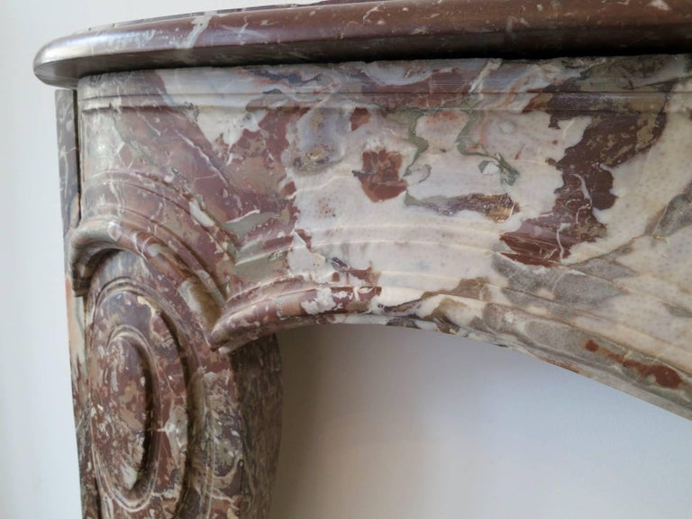 An unusual French fireplace in Rouge Royal marble, in the manner of Louis XV with a serpentine moulded frieze which is supported by inverted cantered jambs with scrolled carving detail to front, mid-late 18th century.   Measures: Opening 113cm W x