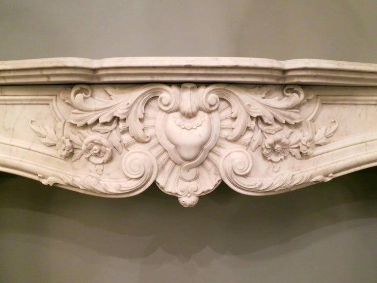 A Louis XV style fireplace in pale Carrara marble, the frieze with a carved central cartouche of C scrolled foliage, flowers and medallion. The end blocks with carved shell and foliate carvings descending into conforming carvings on the jambs with