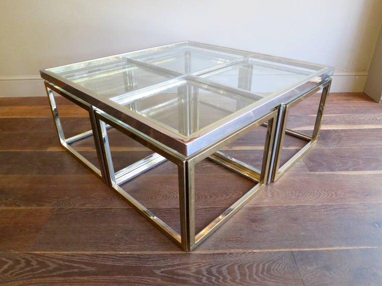 A large square cocktail table with four cubed side tables inside, all in brass and chrome. A very versatile and functional table. Designed by Jean Charles Paris 