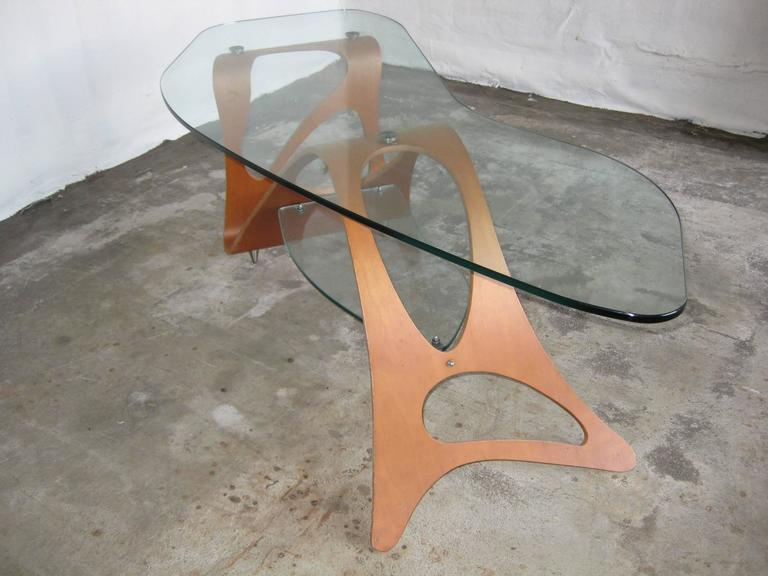 Arabesco coffee table design by Carlo Mollino 1949 for the living room of Casa Orenga in Turin. Plywooly wood legs with glass top. Original Zanotta production.   Manufacture logo in the wooden base.