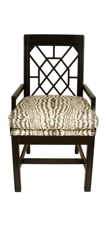 A pair of black painted fretwork chairs with faux bois fabric attached cushions.