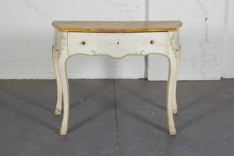 Each with faux marble top of bombe form over a frieze drawer raised on cabriole legs ending in hoof-form feet. Painted in a chalky white with celadon green cartouche decoration and banding. Impressively scaled.