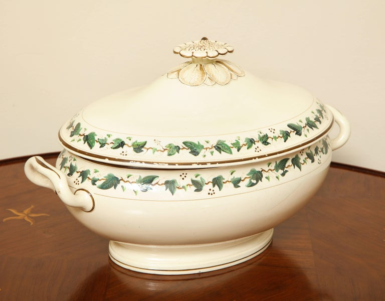 Covered tureen with lid centred by a sepia sunflower head finial and body mounted with two carrying handles; with finely painted ivy vine border within sepia banding.