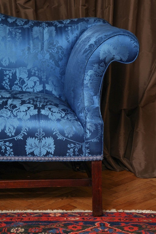 With silk damask-upholstered serpentine back, outward scrolling arms and seat; raised on square legs joined by stretchers; on casters.