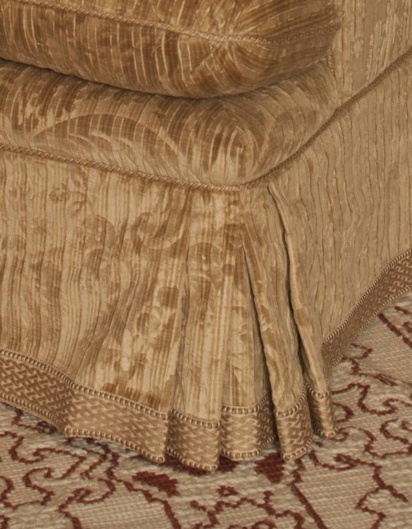With downward scrolling Regency style armrest; double-kick pleated skirt with braid trim and cord in seams; down and foam seat and back cushions. Upholstered in medium brown old world weavers velvet. Bearing Schneller label.  Provenance: Supplied