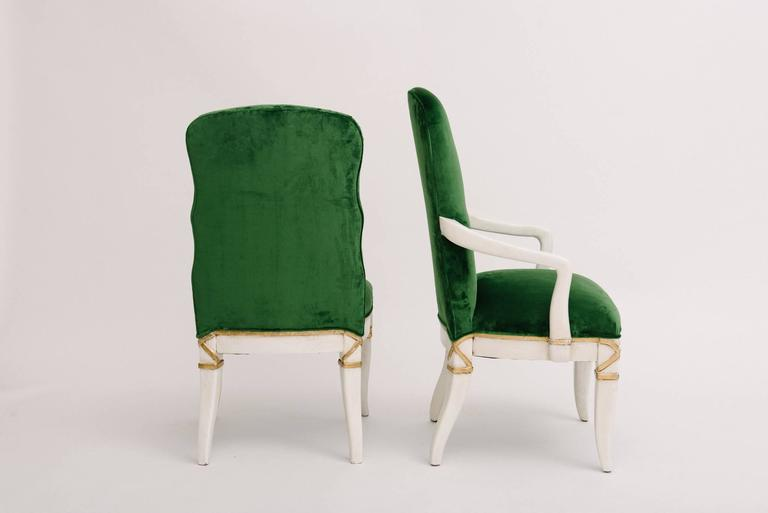 A fabulous set of ten Marge Carson dining chairs. These sturdy and comfortable oak chairs are white painted and gold gilded, rebuilt and restyled in a Rubelli Matora Smeraldo green velvet. A fabric cutting is available upon request.  Measures: Two