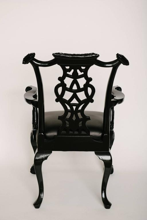 An intricately carved black lacquered 19th century Chippendale style chair newly upholstered in a buttery soft black leather.