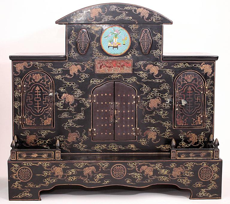 Pair of early 20th century Chinese hand-painted black lacquered ancestral shrines. Each shrine features three sets of double doors, a carved antique gilt panel and a cloisonné center medallion. Measures: 31.5 x 29.