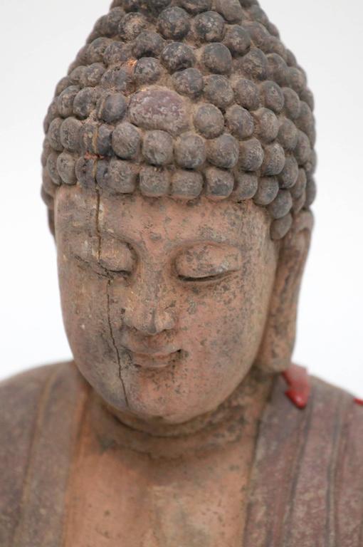 A 25.25 inch tall antique carved polychrome standing Buddha Amitabha. The Buddha of infinite light.
