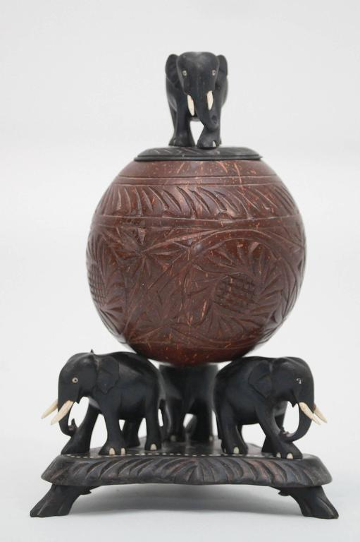 Hand-carved ebony elephants on footed base holding up a carved spherical coconut box and lid.
