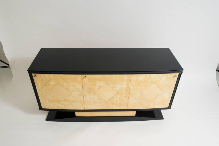 A three-door Art Deco credenza by Vittorio Dassi, Milan, circa 1940s. This beautiful Maplewood server features four centre drawers, bronze key escutcheons and bronze pulls. The cabinet frame and base are black lacquered topped with a piece of black