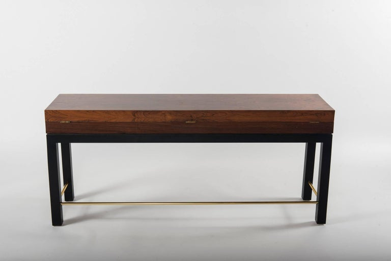 A Bolivian rosewood long chest with ebonized legs and brass stretcher.