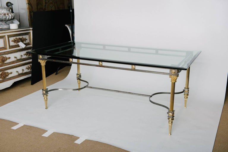 Maison Jansen attributed steel and brass dining table with column supports and a glass top, circa 1970s.