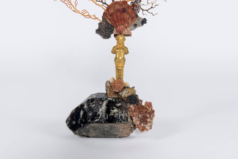 Calypso I sculpture. An early 19th century bronze doré caryatid sits atop a large natural smoky quartz base. Her head is beautifully affixed with a crown adorned by a rare complete lion's paw shell, mixed sea fan corals and minerals. The bounty of