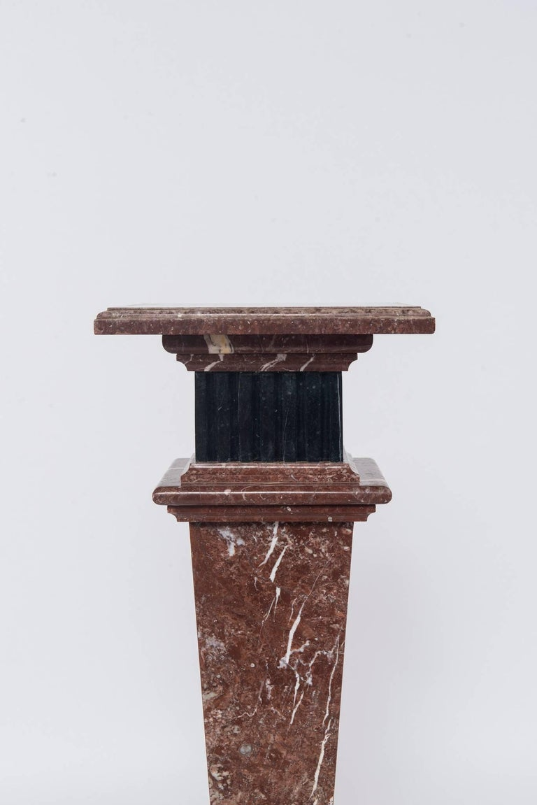 An early 20th century neoclassical style red or rouge and black marble pedestal.