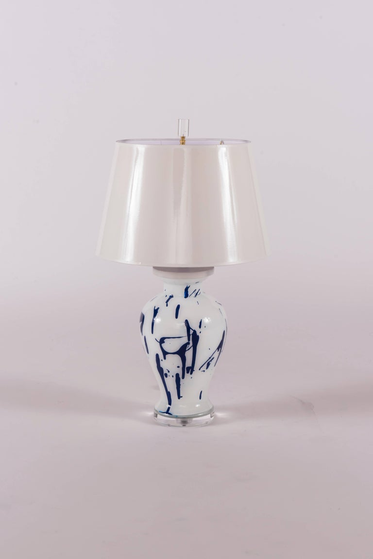A one of kind blue and white Liz Marsh verre églomisé lamp with Lucite base from her Pop collection.  Liz's hand-painted lamps were honoured by Architectural Digest as one of the