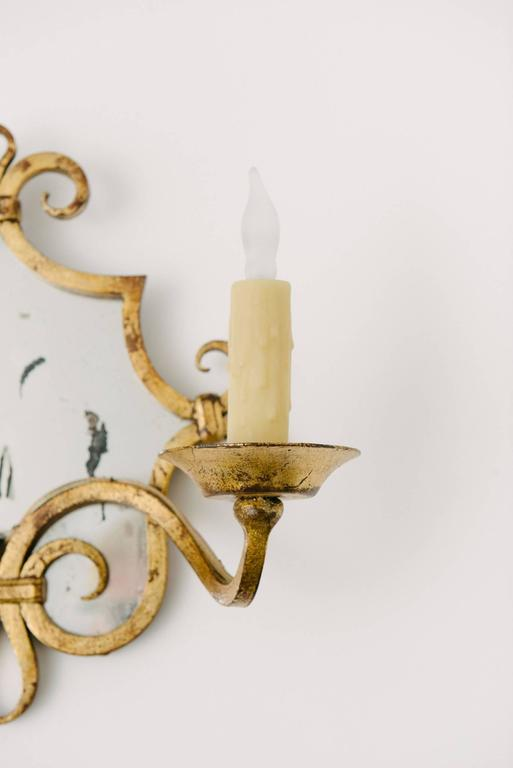 A pair of two-armed gilt iron mirror sconces. Newly rewired.